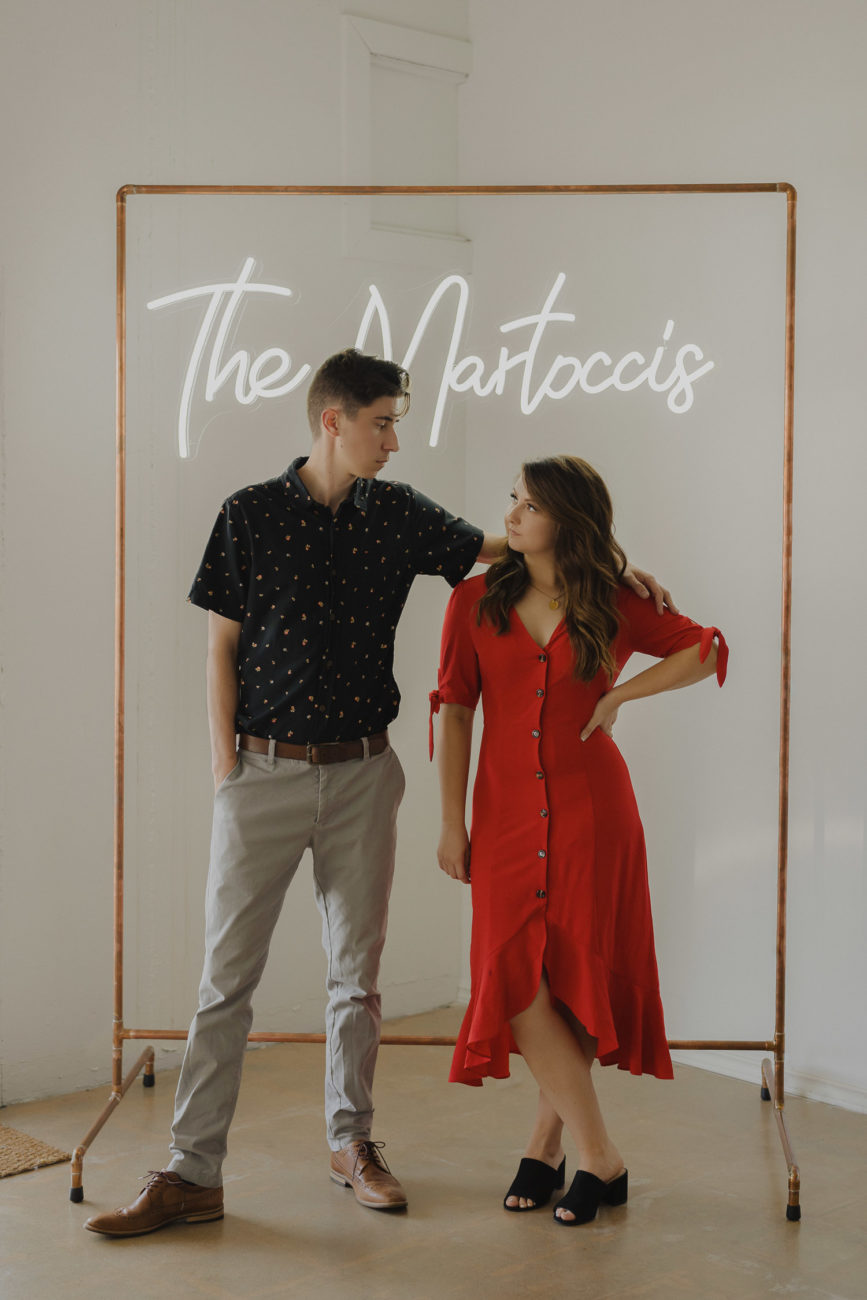 white-and-mexican-couple-with-neon-last-name-sign-copper-frame-red-vintage-dress-outfit-inspo