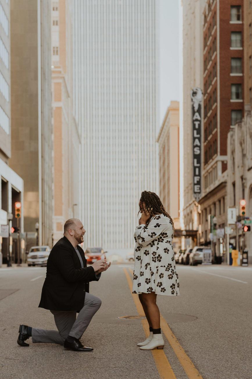 downtown-tulsa-5th-boston-proposal-in-street-interracial-couple-sunset-down-on-one-knee-tulsa-wedding-photographer