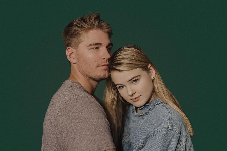 couple-posing-in-studio-green-background-jean-jacket-blonde